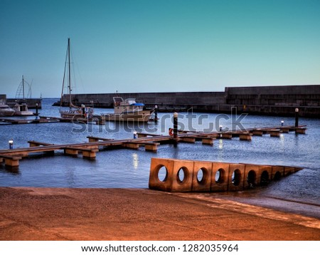 Little harbour mall with small ships in Madeira, Portugal before sunset, Ponta do Sol, Câmara de Lobos, Ribeira Brava, Funchal, darkness, flagstaff #1282035964
