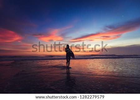 Girl walking in sunshine in warm evening sun holding surfboard. Water sport summer vacation travel concept.  #1282279579