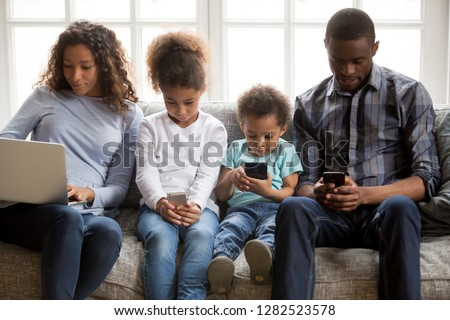 African american family with kids using laptop and mobile phones at home, black parents and little children addicted to devices, gadgets dependence overuse, internet social media addiction concept #1282523578