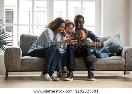 Happy african family with 2 children son daughter having fun with gadget on couch using smartphone at home, black parents and kids laugh watch funny video, make video call selfie on phone online app #1282523581