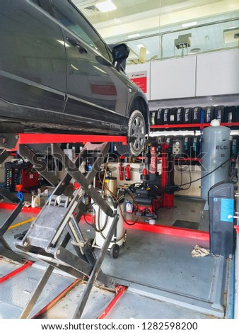 January 12, 2019 - Abu Dhabi, UAE: Sedan car on hydraulic stand for oil change and service #1282598200