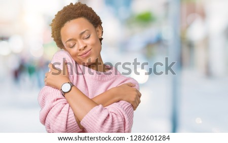 Beautiful young african american woman over isolated background Hugging oneself happy and positive, smiling confident. Self love and self care #1282601284