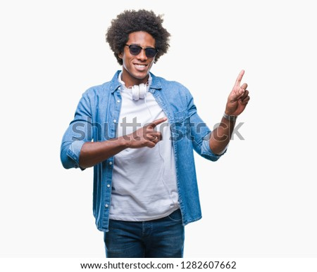 Afro american man wearing headphones listening to music over isolated background smiling and looking at the camera pointing with two hands and fingers to the side. #1282607662