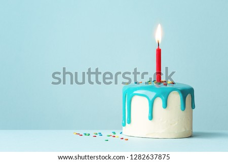 Birthday cake with one red candle and drip frosting Royalty-Free Stock Photo #1282637875
