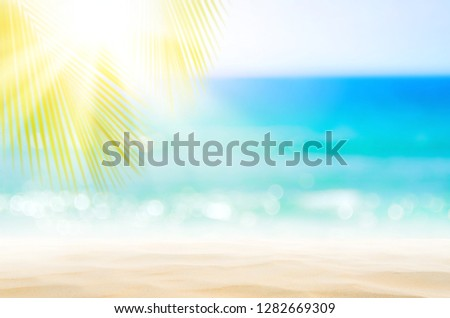 Blur beautiful nature green palm leaf on tropical beach with bokeh sun light wave abstract background. Copy space of summer vacation and business travel concept. Vintage tone filter effect color style #1282669309