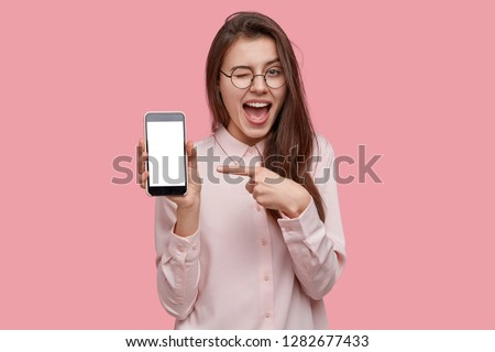 Look at this cell phone! Pleased happy woman blinks eyes, points with index finger at blank screen, shows modern device, dressed in fashionable shirt, isolated over pink background. Technology concept #1282677433