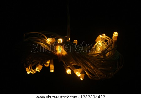 yellow fairy lights wrapped in infinity shape #1282696432