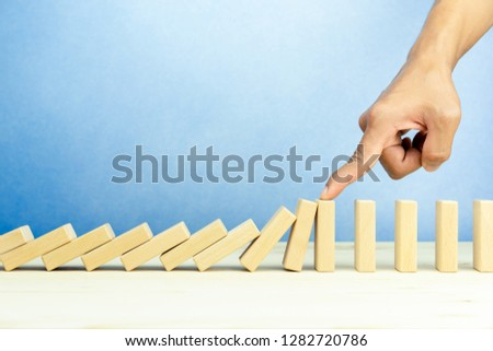 Businessman hand stopping falling wooden blocks, dominoes effect, risk and strategy concept. copy space #1282720786