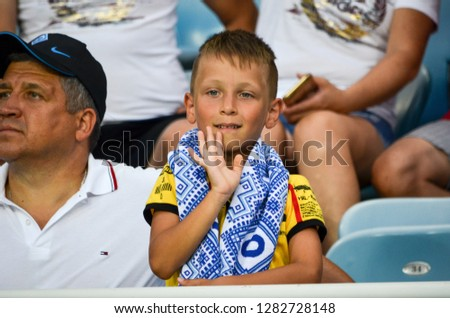 ODESSA, UKRAINE - July 21, 2018: Football fans and ultras seat on the stand during the finals of the Ukrainian 2018 Supercup between Shakhtar Donetsk and Dinamo Kiev, Ukraine #1282728148