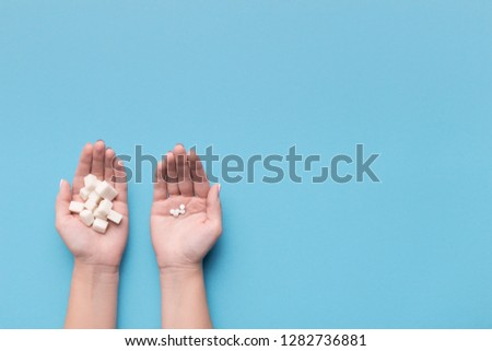 Female hands with sugar and pills on blue background. Choice of sweetener in tablets or regular sugar. Alternative to sugar for diabetics. #1282736881