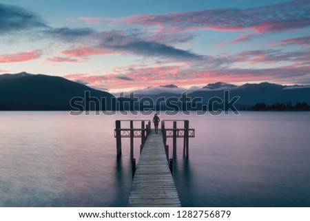Woman Silhouette in Romantic wharf on Te Anau on South Island of New Zealand Beautiful pier on sunrise.  Lake Te Anau is the largest lake in the South Island  #1282756879