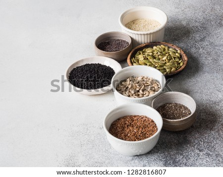 Various seeds - sesame, flax seed, sunflower seeds, pumpkin seed, poppy, chia in bowls on a gray background. Copy space.  #1282816807