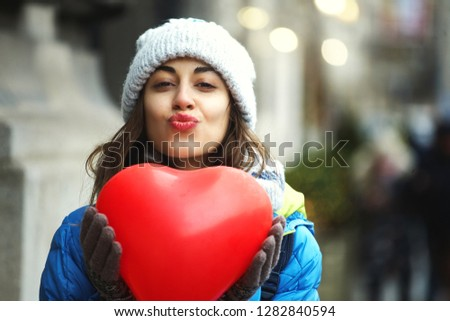 horizontal image of a cheerful young woman with a heart shaped red balloons. woman blows kiss, demonstrates her good feelings, says Love you on distance. Young pretty female model makes air kiss
