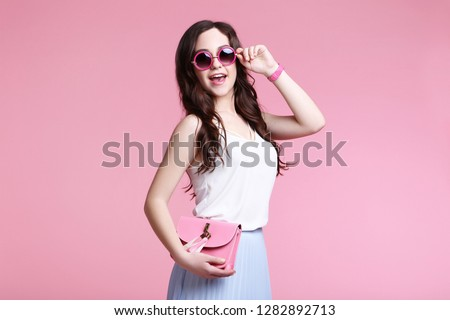 Beautiful young woman with handbag on pink background #1282892713