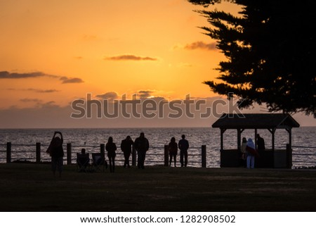 Colorful orange and purple sunset on the Pacific Ocean in La Jolla, San Diego California with silhouettes of people enjoying the evening. May 7, 2018 - La Jolla, California #1282908502