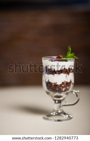 Yogurt with cream, strawberry and muesli served in glass on the table #1282940773