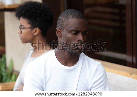 Unhappy couple sitting on couch, focus on serious sad american man thinking about difficulties in relationship, spouses not looking at each other and not talking, being in quarrel. Break up concept #1282948690