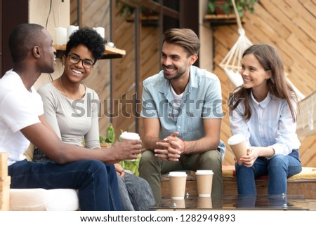 Four laughing diverse people positive multi-ethnic friends sitting in cozy cafe summer terrace drink coffee telling funny stories from life feels happy and satisfied enjoy time together on weekend #1282949893
