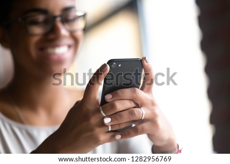 Happy smiling black african woman holds mobile phone, close up focus on female hands and device. Customer buying goods via internet, friends chatting online, generation addicted with gadgets concept