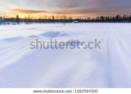 Winter sunset in Finnish Lapland with log cabin and forest in the background, deep snow in the foreground. Picture taken in Pyha, Finland.