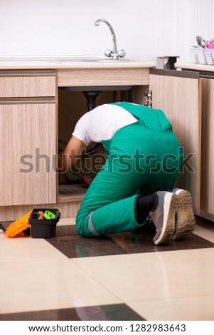 Young plumber repairing wash basin at kitchen   #1282983643