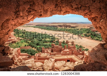 Popular point of view of the valley of the desolating river Onila through a hole in a wall of Ancient Kasbah in Ait-Ben-Haddou, Morocoo. Famous ancient berber kasbah. near Ouarzazate city in Morocco #1283004388