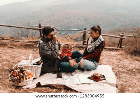 Mixed race man holding poodle in the lap while taking picture of his beautiful girlfriend. Both sitting on the blanket, autumn time.