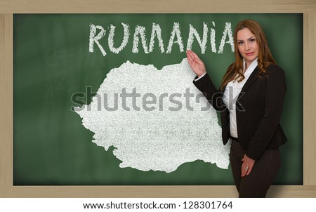 Successful, beautiful and confident young woman showing map of romania on blackboard for presentation, marketing research and tourist advertising #128301764