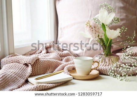 Cozy Easter, spring still life scene. Cup of coffee, opened notebook, pink knitted plaid on windowsill. Vintage feminine styled photo. Floral composition with tulips, hyacinth and Gypsophila flowers. #1283059717