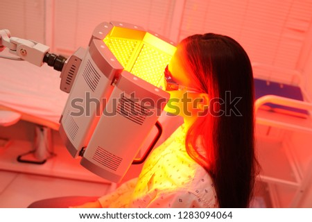 red light therapy. The girl goes through a course of skin rejuvenation with the help of red light treatment. #1283094064