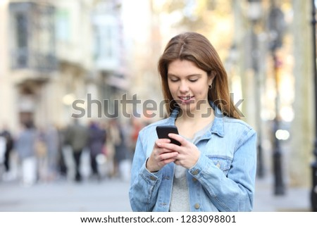 Portrait of a happy teen texting messages on a smart phone in the street #1283098801