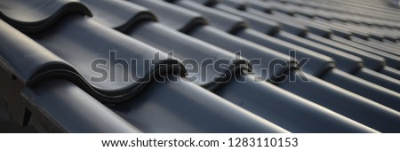 icon roof with new black roofing tiles double flap on residential property. banner on the roof for roofers Royalty-Free Stock Photo #1283110153