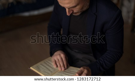 brave 45 years old men with gray hair and beard in dark navy suit reading a book #1283172712