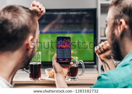 Two male buddies watching live football game broadcast on tv and celebrating money win after making bets online at bookmakers website. #1283182732