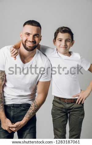 happy father and his adorable little son smiling at camera isolated on grey background. close up shot. studio shot. #1283187061