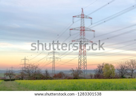power lines at sunset, overhead power line pylon, power line pylon with ground wire, equipment for overhead power line pylons #1283301538