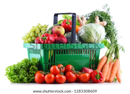 Fresh organic fruits and vegetables in plastic shopping basket isolated on white #1283308609