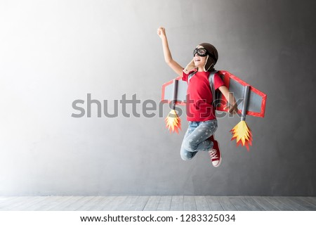 Happy child playing with toy jetpack. Kid pilot having fun at home. Success, innovation and leader concept #1283325034