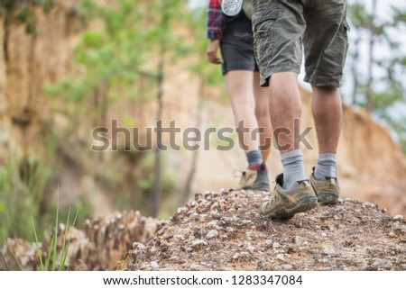 Group of man and women are walking trough forest path wearing mountain boots and walking sticks. Low section view. #1283347084