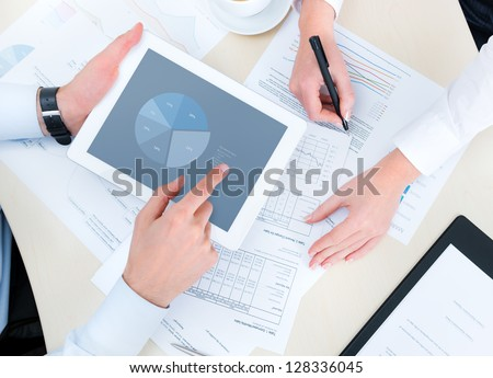 Business people developing a business project and analyzing market data information on a modern digital tablet computer. Top view photo shoot.