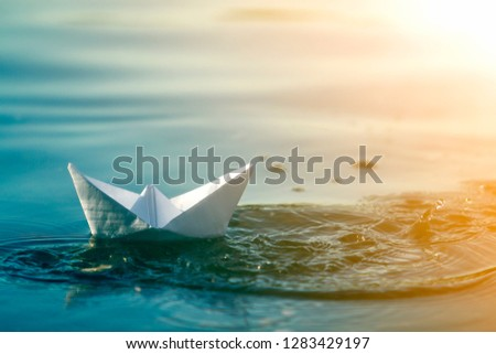 Close-up of simple small white origami paper boat floating in blue clear river or sea water under bright summer sky. Beauty of nature, freedom, dreams and fantasies concept. #1283429197