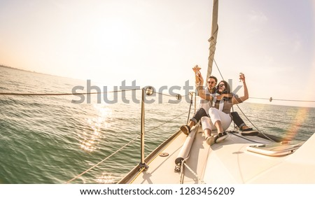 Young lovers couple on sail boat with champagne at sunset - Exclusive luxury concept with rich millennial people lifestyle on tour around the world - Soft backlight focus on warm sunshine filter #1283456209
