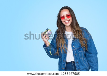 Laughing teenage girl in denim and sunglasses holding vintage camera and laughing on blue background #1283497585