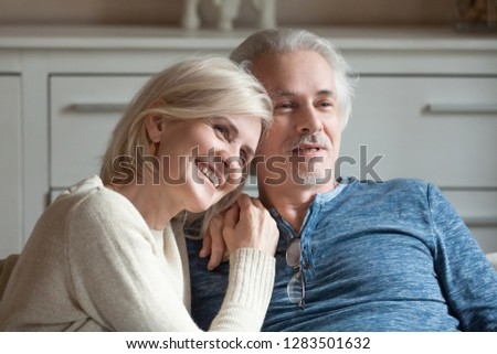 Close up positive healthy middle aged spouses grey haired wife and husband embracing sitting together on comfortable couch in living room at home looking away planning weekend or watching television #1283501632