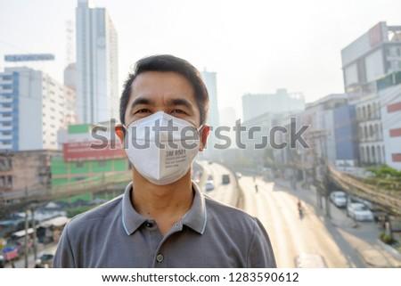BANGKOK, THAILAND - January 14: Dindang road on January 14,2019 in Bangkok, Thailand. Asian man wearing the N95 Respiratory Protection Mask against air pollution at road and traffic in Bangkok #1283590612
