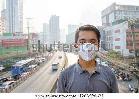 BANGKOK, THAILAND - January 14: Dindang road on January 14,2019 in Bangkok, Thailand. Asian man wearing the N95 Respiratory Protection Mask against air pollution at road and traffic in Bangkok #1283590621