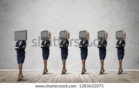 Businessmen in suits with old TV instead of their heads keeping arms crossed while standing in a row and one at the head with TV in empty room against gray wall on background. #1283632075