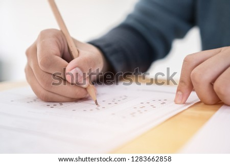 Education test exam concept, high school / university student holding pencil writing paper answer sheet on lecture chair for taking exams in examination room or classroom. Educational assessment ideas #1283662858