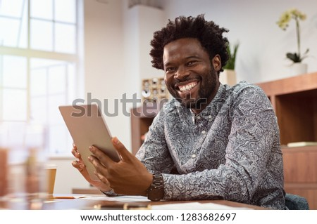 Happy casual african man using digital tablet at office. Portrait of smiling black businessman sitting on chair using tablet pc. African american casual business man looking at camera. #1283682697