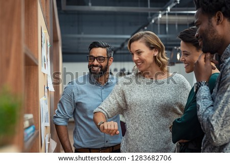 Group of mature businesspeople planning business strategy while looking at infographic on wall. Business men and casual women looking at pie charts. Successful startup partners feeling happy. #1283682706